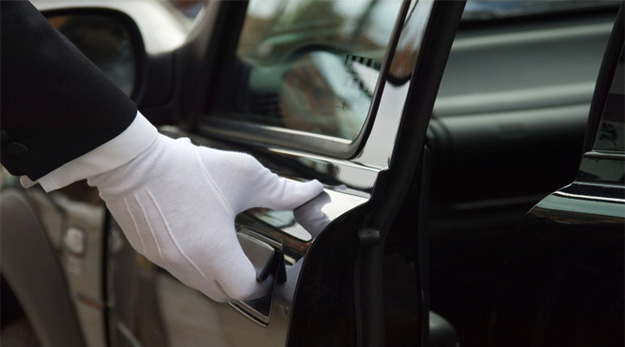 A gloved hand opening a limo door